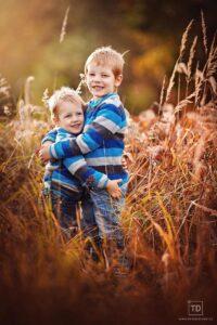 Rodinná fotografie dětí v trávě fotografa Tomáše Drozda Ostrava